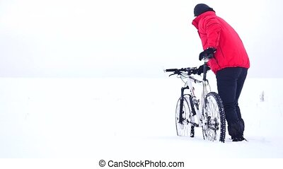 Man with mountain bike on snowy filed. Biker is pushing bike...