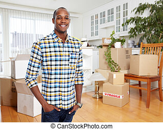 Man with moving boxes in new apartment.