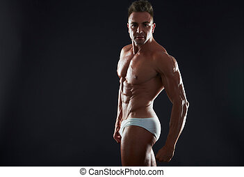 Man with muscular torso. Strong Athletic Man Fitness Model...
