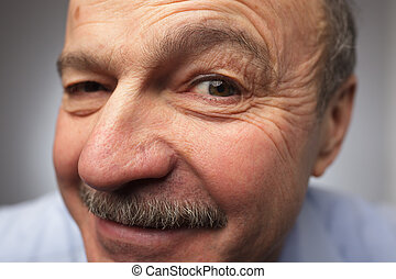 Man with mustache looking at the camera winking, keeping secret