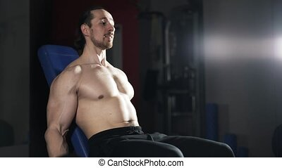 Man with naked torso doing a dumbbell exercise in gym