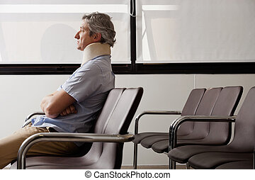 Man With Neck Injury Waiting In Lobby - Side view of mature...