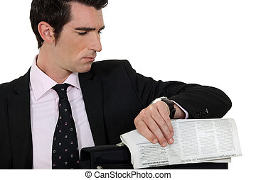 Man with newspaper looking at watch