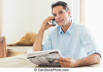 Man with newspaper using cellphone in kitchen
