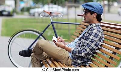 man with notebook or diary writing on city street