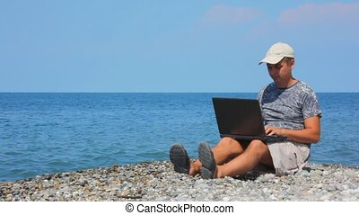 man with notebook sitting on pebble beach, sea in background