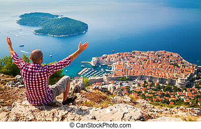 man with opened arms looking down to the Old Town of Dubrovnik