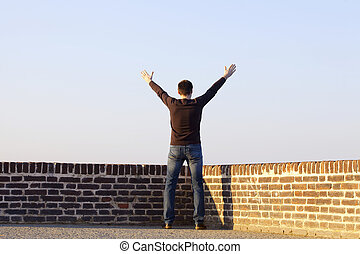 man with outstretched arms standing against the sky