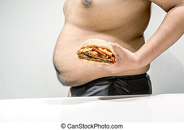 Man with overweight belly holding hamburger on his hand