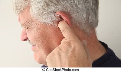 man with pain in ear - an older man suffering from pain deep...