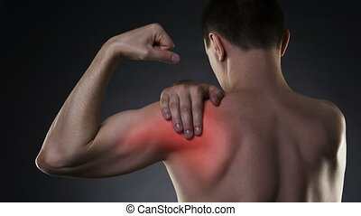 Man with pain in shoulder on black background