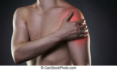 Man with pain in shoulder on black background, studio shot...