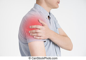 Man with pain in shoulder on gray background