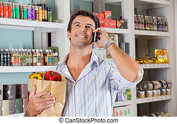 Man With Paper Bag Using Cellphone In Market