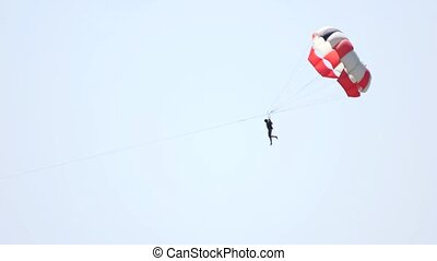 Man with parachute over the sky background. Activities at...