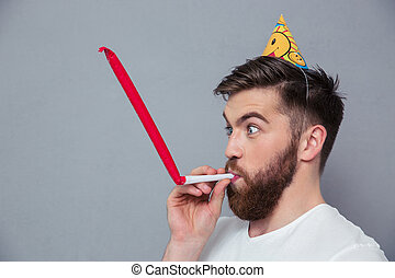 Man with party hat blowing in whistle
