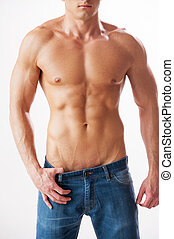 Man with perfect torso. Close-up of young muscular man with perfect torso standing against white background