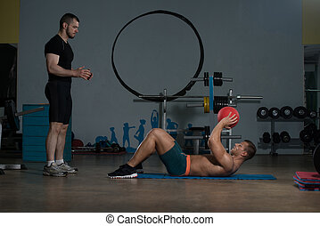 Man With Personal Trainer At Medicine Ball Exercises