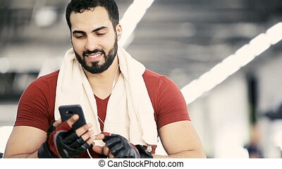 Man with Phone in Gym - Handsome muscular man wears red...