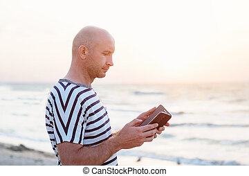 Man with phone on the seashore