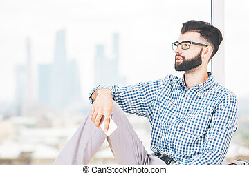 Handsome young man with mobile phone in hand sitting on windowsill with blurry city view