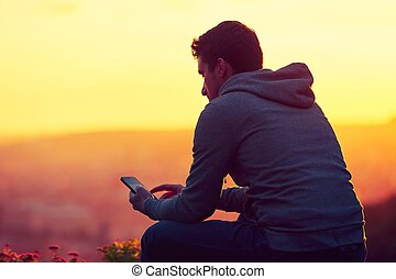 Man with phone - Young man with phone at the sunrise.