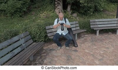 Man with photo camera on bench in the park
