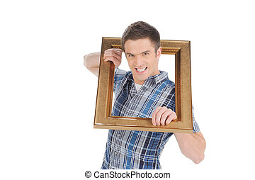 Man with picture frame. Handsome young man getting out of the picture frame and grimacing while isolated on white