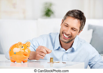 Man With Piggybank Counting Coins At Table - Handsome mature...