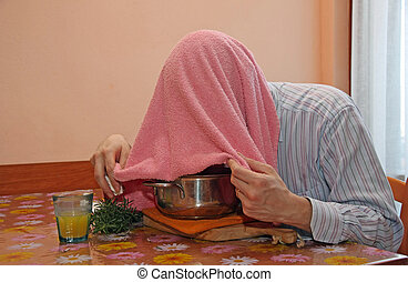 man with pink towel breathe balsam vapors to treat colds and the flu