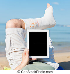 Man with plaster lying on the beach with Ipad