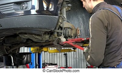 man with pliers tongs repair car hanging on lift brake...