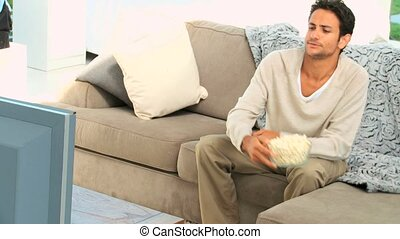 Man with popocorn watching a match in his living room