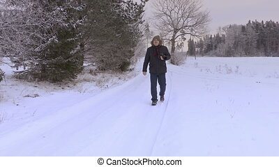 Man with professional photo camera on snow covered road in winter