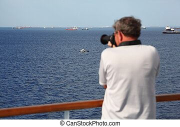 man with professional photo camera standing on deck of cruise ship and shooting ships. focus on ships.