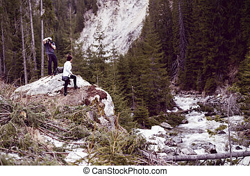 man with professional photo camera taking picture of a tourist woman on the mountains