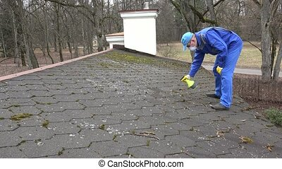 man with protective clothes and respirator spray moss with chemicals on roof.