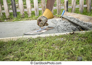 Man with protective gloves levelling the surface of a concrete plate