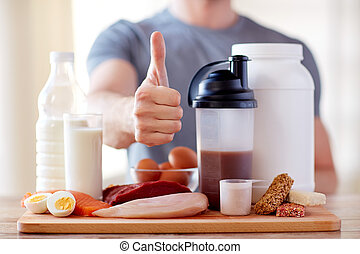 man with protein food showing thumbs up - sport, fitness,...