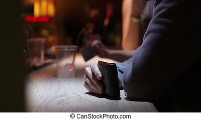 man with purse waiting a drink on bar