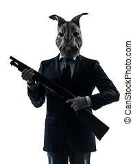 man with rabbit mask hunting with shotgun silhouette portrait