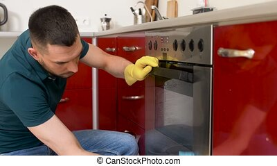 man with rag cleaning oven door at home kitchen - household...