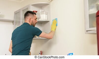 man with rag cleaning wall at home kitchen - household and...