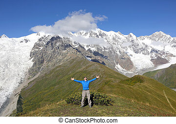 man with raised hands standing on the background of snowy mountains