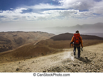 man with red backpack on rocky path in desert