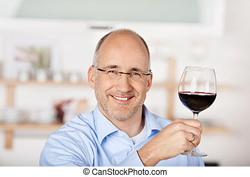 Man with red wine - Smiling man showing the red wine at home