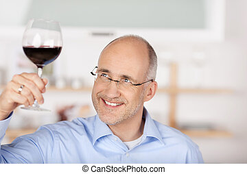 Man with red wine - Smiling mid age man looking at the red ...