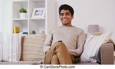 man with remote control watching tv at home - people,...