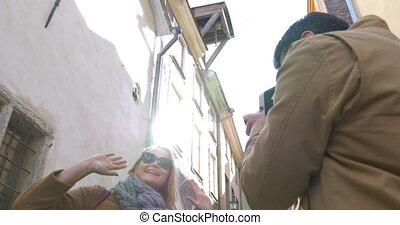 Man with retro camera shooting flirty blonde