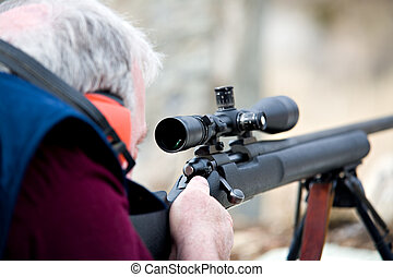 man with rifle - man laying down with rifle, taking aim....
